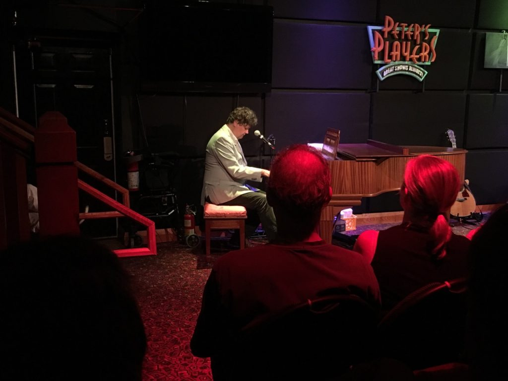 Man playing piano in front of small crowd