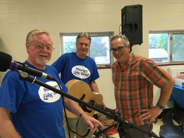 Three smiling men and a guitar