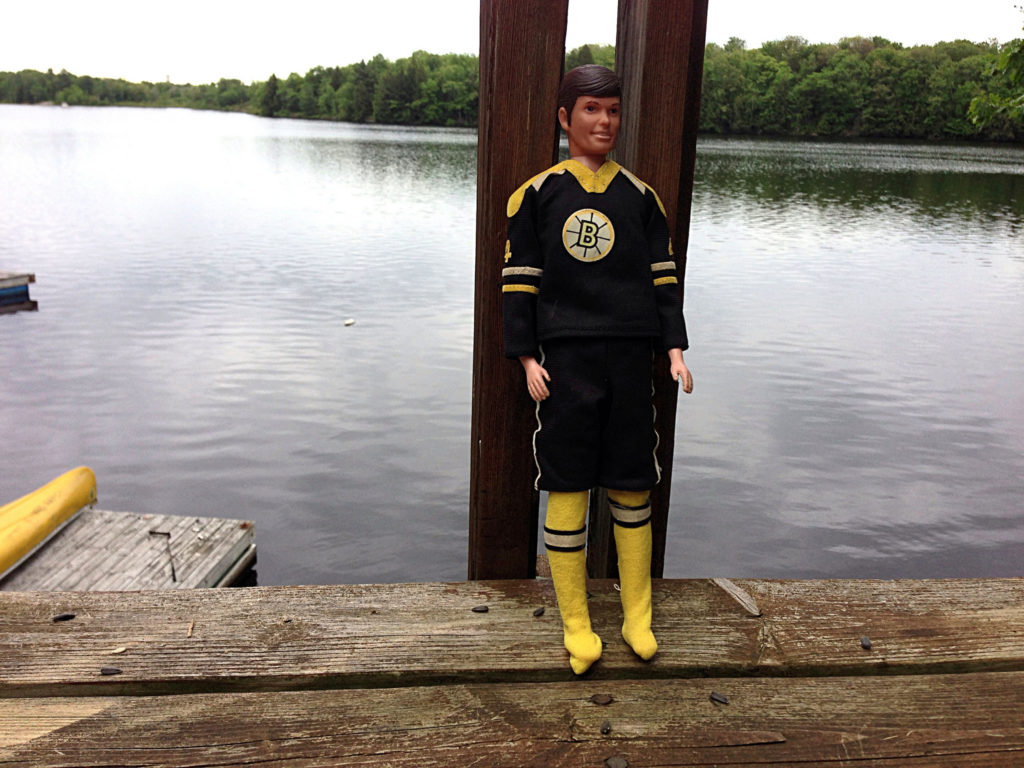 Bobby Orr doll on a deck at the lake