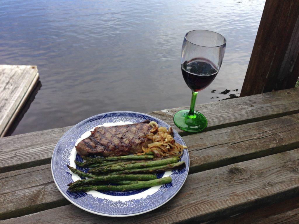Steak wine and asperagus on dock by lake