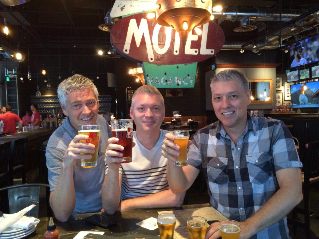 three men holding beer at a bar