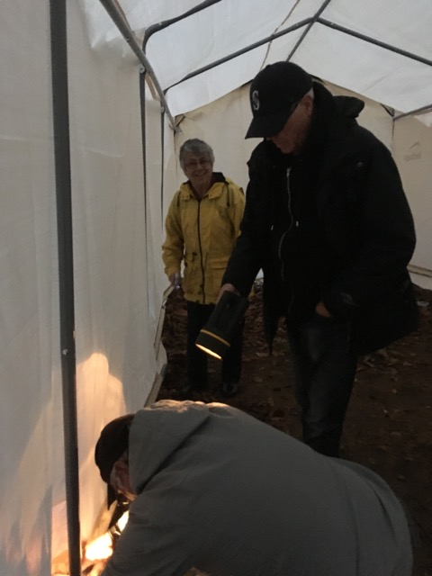 Three people building a tent