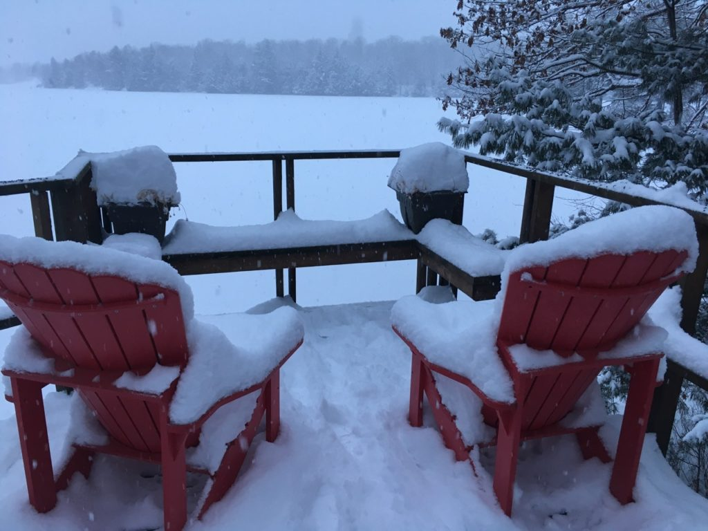 snow on red deck chairs