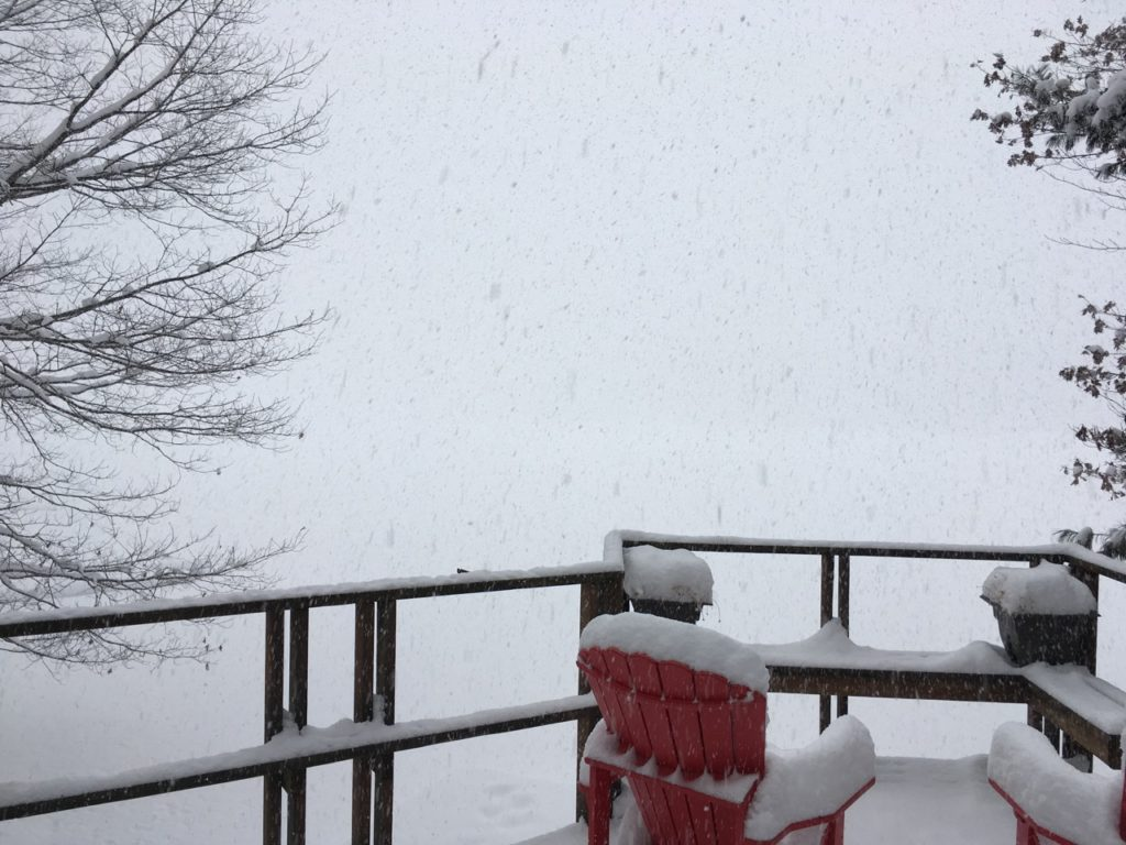snow falling on deck and red deck chairs