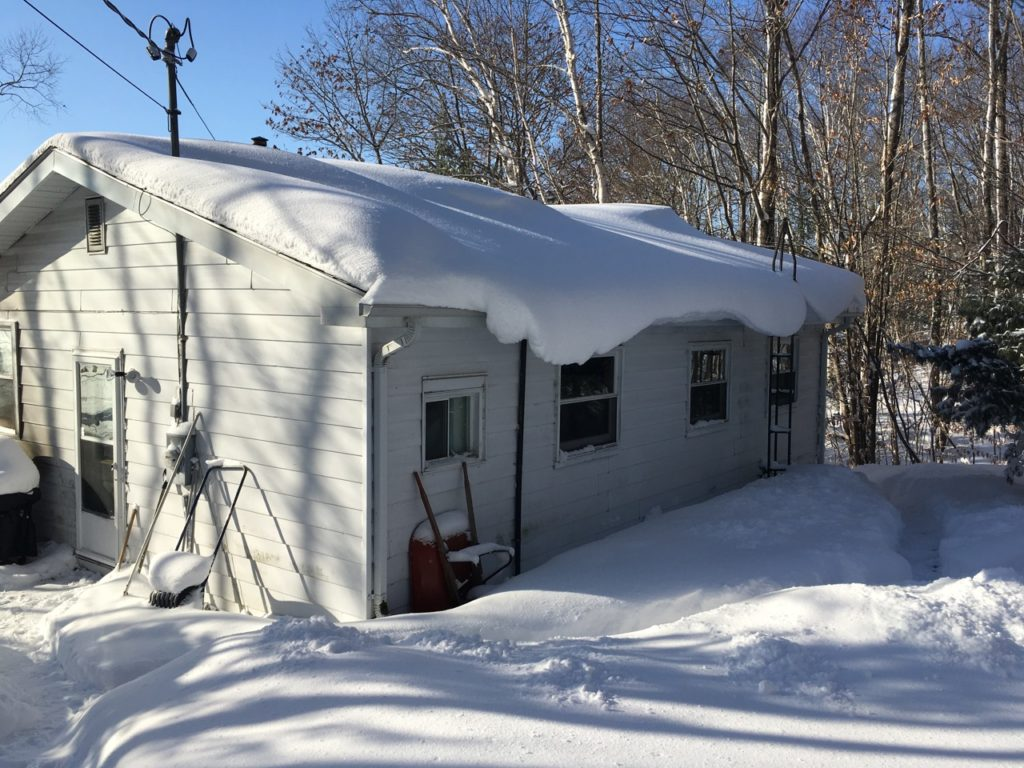 lots of snow on a cottage roof