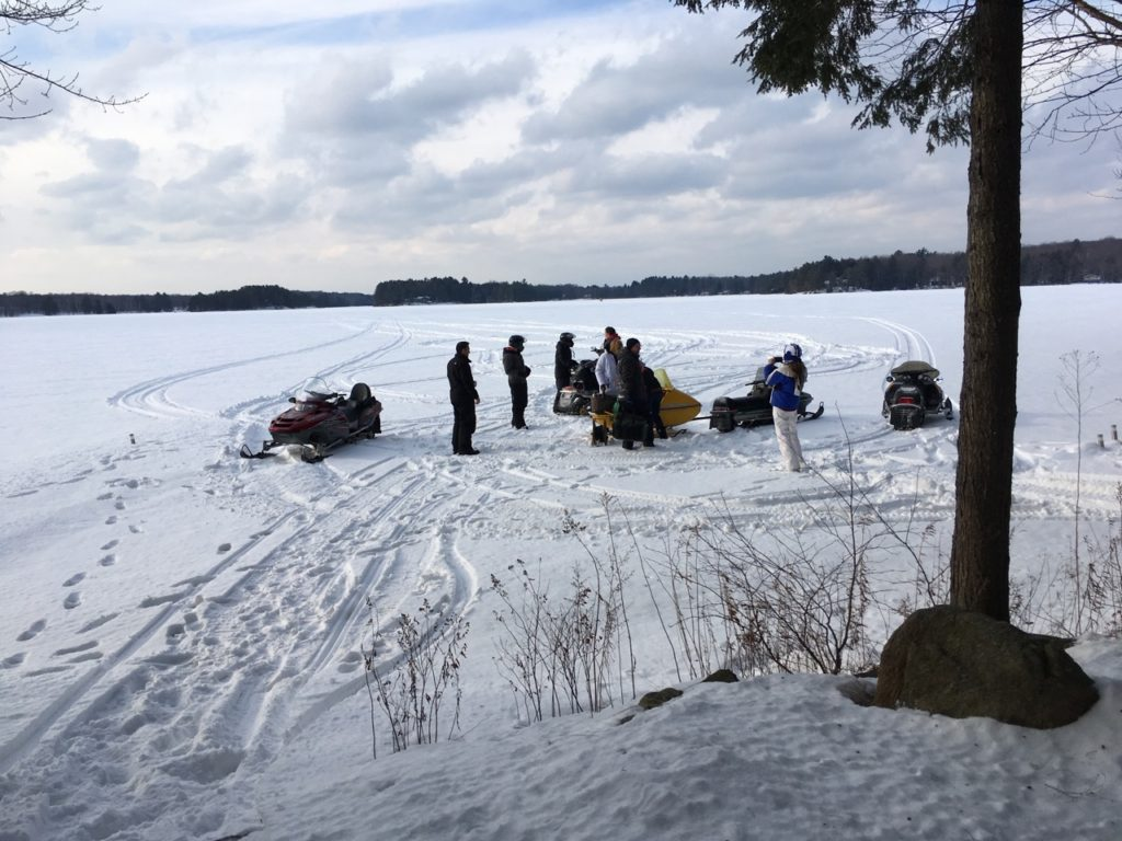 snowmobiles and people on snowy lake