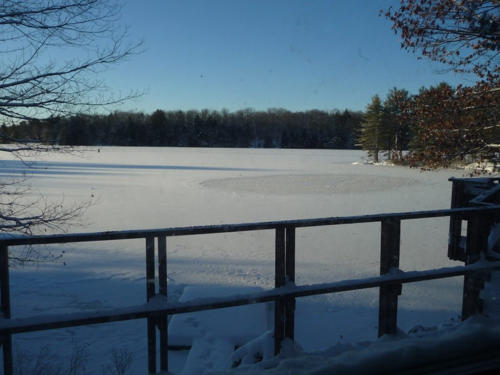 frozen lake seen from a cottage deck