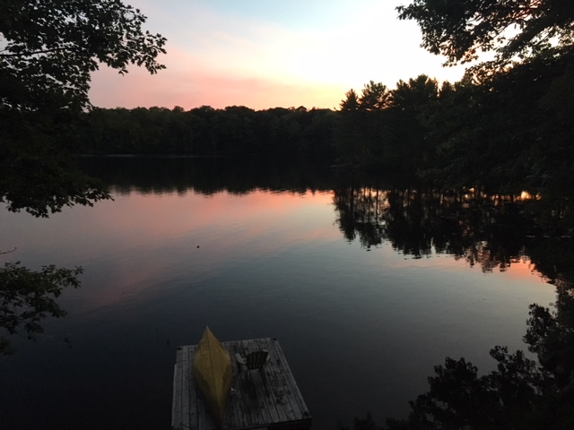 lake at twilight with canoe on dock